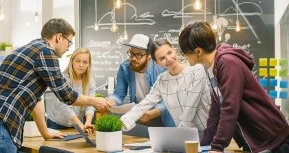 Ein junges Team arbeitet an einem Tisch mit einer Cloud ERP Software.