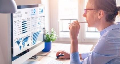 Eine Person sitzt am Rechner und überprüft ihre Website mithilfe von Monitoring auf Fehler.