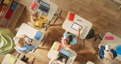 Schultische von oben mit Kindern, die an Laptops, Tablets und Smartphones arbeiten zeigen den Stand der Digitalisierung in der Schule.