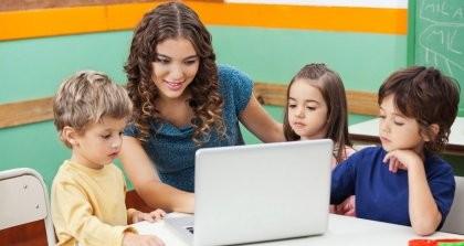 Eine Erzieherin zeigt Kindern etwas am Computer. Die Kinder verwaltet sie mit einer Kindergartensoftware.