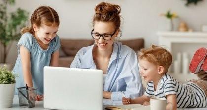 Eine Erzieherin verwendet ein Kita Verwaltungssoftware an einem Laptop und zwei Kinder schauen ihr dabei zu.