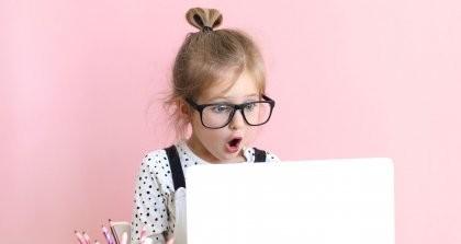 Ein Kind sitzt mit einer großen Brille auf der Nase vor einem Laptop und macht aufgrund von Datenschutz ein entsetztes Gesicht.