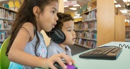 Zwei Kinder sitzen vor einem Rechner und surfen im Web.