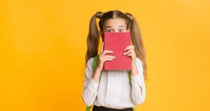 Ein Grundschulkind hält ein Buch vor das Gesicht und schaut mit großen Augen dahinter hervor.