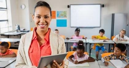 Eine Lehrerin verwendet eine Software für die Verwaltung ihrer Schülerinnen und Schüler auf einem Tablet vor ihrer Klasse.