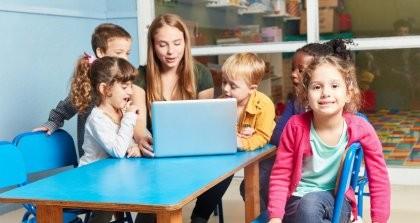 Eine Erzieherin sitzt mit Kindern in der Kita zusammen an einem Laptop.