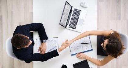 Ein Bewerber und eine Personalleiterin geben sich über einen Tisch die Hand. Neben der Personalleiterin steht ein Laptop mit einem Bewerbermanagementsystem.