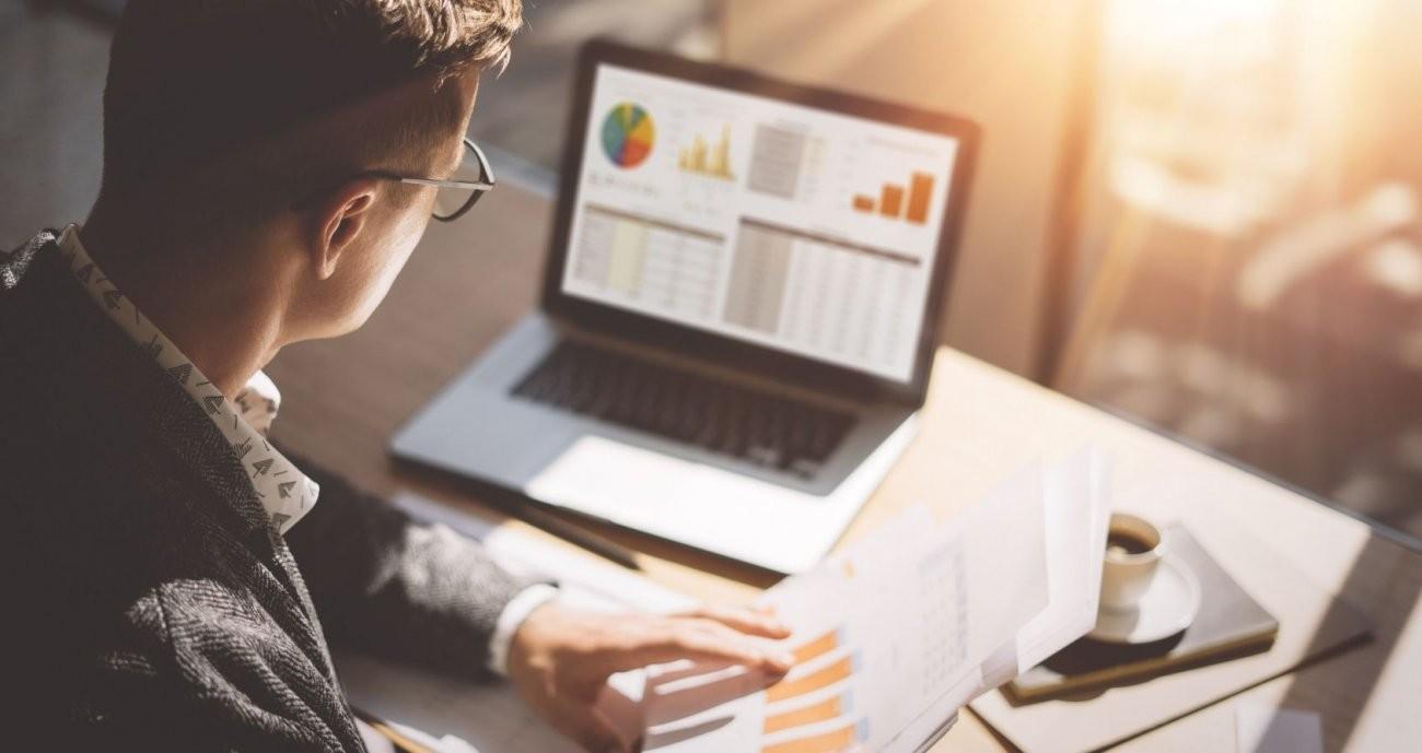 Ein junger Mann schaut auf einen Bildschirm, auf dem er online eine Rechnung erstellt hat.