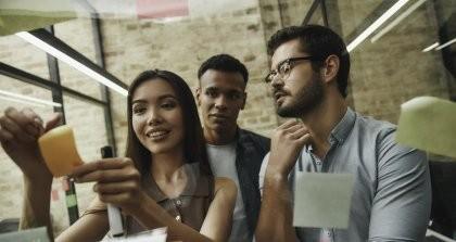 Drei junge Mitarbeiter*innen kleben Zettel an eine Fensterscheibe.