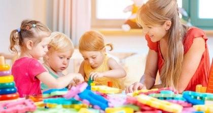 Eine Erzieherin betreut drei Kinder in der Kita beim Spielen.