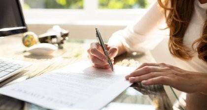 Eine Frau sitzt am Schreibtisch und unterschreibt einen Vertrag.