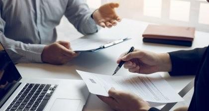 Zwei Personen sitzen an einem Schreibtisch und schreiben ein Angebot.