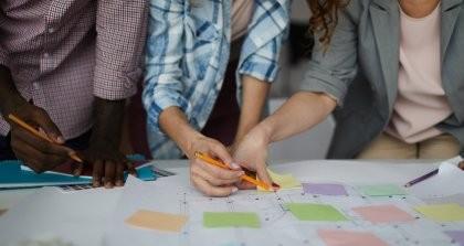 Vier Menschen zusammen an einem Schreibtisch, die planen und Tabellen auswerten