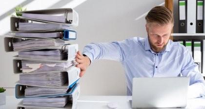 Mann am Schreibtisch mit Laptop und Aktenordnern