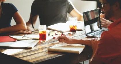 Menschen im Büro mit Getränk am Laptop