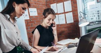 Zwei Frauen notieren etwas und arbeiten am Schreibtisch