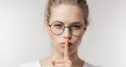 Geheimnisvolle Frau hält sich einen Finger vor den Mund