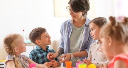Vier Kinder spielen mit einer pädagogischen Fachkraft