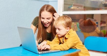 Erzieherin und kleiner Junge sitzen vor einem Laptop