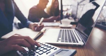 Eine Person erstellt online Rechnungen in einem Café an ihrem Laptop mit Taschenrechner.